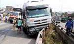 Xe container nằm vắt vẻo trên thành cầu, tài xế bung cửa thoát thân