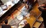 Nhân viên nhà hàng rửa đĩa trong vũng nước ngoài đường