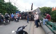 Xe tải chở gạch lật ngang trên cầu