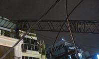 Cần cẩu hàng chục mét gãy, 'vắt' lên sân thượng nhà dân đối diện công trình