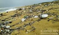 Quảng Nam: Dầu vón cục bám trên rác trôi dạt vào bờ biển