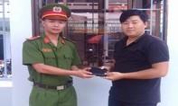 Một hạ sĩ quan công an trao ví lại cho người mất