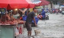 Tiểu thương vừa bán hàng vừa chống ngập trong mưa lớn