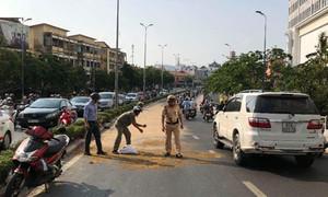 Nhiều người té vì nhớt máy tràn đường, CSGT cùng dân dọn sạch