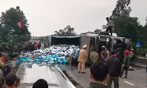 Xe container lật nhào, hàng trăm thùng sữa đổ ra đường
