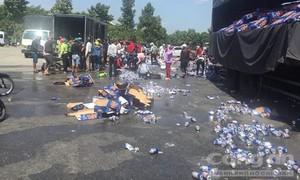 Xe tải chở bia Tiger lật, hàng trăm thùng bia rơi vãi trên đường