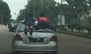 Clip người cha cho hai con đu bám trên đuôi xe chạy tốc độ cao