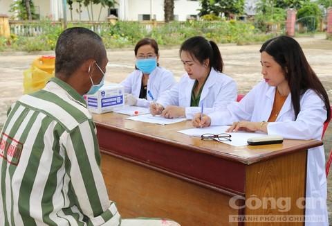 Thượng úy Nguyễn Thị Diệu Thuần (giữa) - cán bộ y tế Trại giam Thủ Đức và 2 bác sĩ của Trung tâm phòng chống HIV/AIDS Bình Thuận hỏi han tình hình sức khỏe và khám chữa bệnh cho phạm nhân