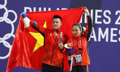 Lại Gia Thành (bên phải) và Vương Thị Huyền (cử tạ nữ) ăn mừng chiến thắng.