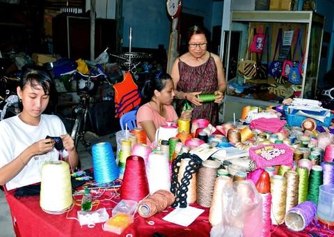 Bà Hoa hướng dẫn các thành viên khuyết tật đan, móc len