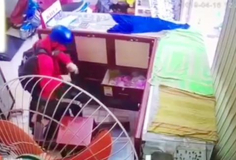 Phương đang gom tiền và vàng trong cửa tiệm. Ảnh cắt từ camera
